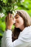 美丽的嗅到的妇女年轻人 免版税图库摄影