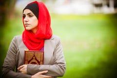 美丽的回教妇女佩带的hijab和拿着一部圣经古兰经 免版税库存图片