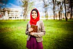 美丽的回教妇女佩带的hijab和拿着一部圣经古兰经 库存图片