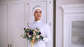 美丽的回教新娘与在与白色头饰的婚礼礼服组成 影视素材
