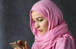 美丽的回教阿拉伯妇女收到在智能手机的正文消息 图库摄影