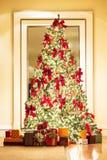 美丽的圣诞树和礼物在金黄屋子里 库存图片