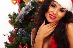 美丽的圣诞老人帮手-在圣诞树旁边 免版税库存图片