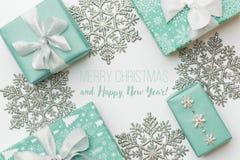 美丽的圣诞节在白色背景隔绝的礼物和银色雪花 绿松石色的被包裹的xmas箱子 免版税库存照片