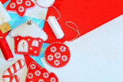 美丽的圣诞节装饰 毛毡房子、圣诞树、星、球,棒棒糖装饰,红色和白色螺纹,在毛毡的针 图库摄影