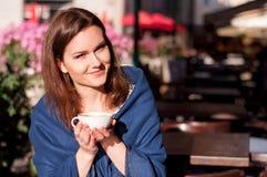 年轻美丽的在一个室外咖啡馆的妇女饮用的早晨咖啡 库存照片