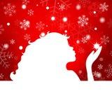 美丽的在一红色backgro的女孩吹的雪花剪影  免版税库存照片