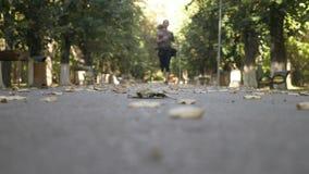 美丽的在公园及早在一个秋天早晨停留激活和适合的少年女性跑步- 股票录像