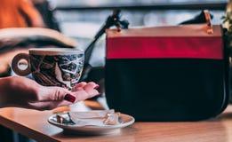 美丽的在咖啡馆的妇女饮用的咖啡 图库摄影
