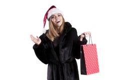 美丽的在圣诞老人帽子假日礼服的女孩年轻模型隔绝了情感时尚 免版税库存图片