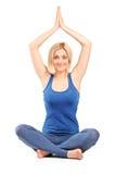 美丽的在地板上供以座位的女孩实践的瑜伽 免版税库存图片