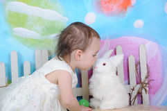 美丽的在复活节时间的小孩亲吻的兔宝宝 免版税图库摄影