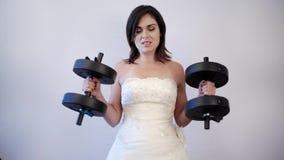 美丽的在她的婚礼礼服的新娘举的重量 股票视频