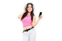 美丽的在她的手机的女孩听的音乐 免版税库存照片