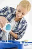 美丽的在容器的妇女倾吐的油漆 免版税库存图片