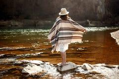 美丽的在岩石的妇女旅客后面身分在河、佩带的帽子和雨披, boho旅行概念 库存照片