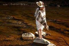 美丽的在岩石的妇女旅客后面身分在河, wearin 库存图片