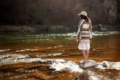 美丽的在岩石的妇女旅客后面身分在河, wearin 库存照片