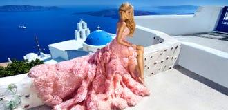 美丽的在惊人的婚礼礼服的新娘白肤金发的女性模型在圣托里尼海岛上摆在希腊 免版税库存照片