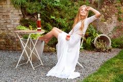 美丽的在户外咖啡馆的妇女饮用的酒 年轻白肤金发的秀丽画象在获得的葡萄园里乐趣,享用a 库存图片