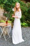美丽的在户外咖啡馆的妇女饮用的酒 年轻白肤金发的秀丽画象在获得的葡萄园里乐趣,享用a 图库摄影