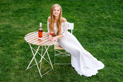 美丽的在户外咖啡馆的妇女饮用的酒 年轻白肤金发的秀丽画象在获得的葡萄园里乐趣,享用a 免版税库存照片