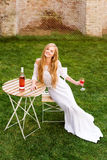 美丽的在户外咖啡馆的妇女饮用的酒 年轻白肤金发的秀丽画象在获得的葡萄园里乐趣,享用a 免版税图库摄影