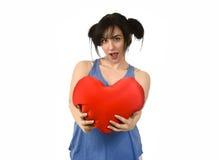 美丽的在拿着红色心脏形状枕头的爱的妇女微笑的愉快的感觉 库存照片