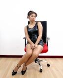 美丽的在椅子的妇女性感的黑礼服 免版税图库摄影