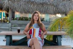 美丽的在海滩的年轻女人饮用的汁液 图库摄影
