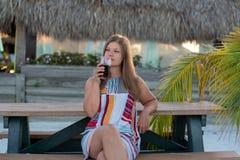 美丽的在海滩的年轻女人饮用的汁液 库存图片