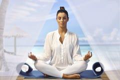 美丽的在海滩的女子实践的瑜伽 免版税图库摄影