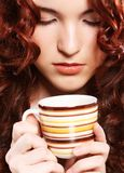 美丽的在米黄backgound的妇女饮用的咖啡 库存图片