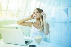 年轻美丽的在耳机的女实业家听的音乐在o 免版税库存照片