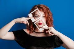 美丽的在蓝色五颜六色的背景的红头发人卷曲妇女吹的嘴唇亲吻 在一只眼睛,拿着卡片的手的构成 免版税库存图片
