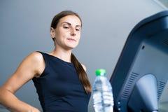 美丽的在踏车的健身女孩跑的和饮用水在健身房 免版税库存照片