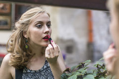 美丽的在镜子附近的妇女佩带的唇膏 库存照片