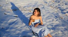 美丽的在雪的女孩饮用的茶在冬天 免版税库存照片