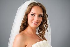 美丽的在面纱之下的新娘微笑的工作&# 免版税图库摄影