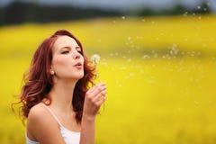 美丽的在领域的妇女吹的蒲公英 库存图片