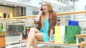 美丽的在购物中心的女孩坐的长凳,谈话  股票录像