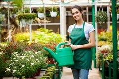 年轻美丽的在blury室外背景的卖花人浇灌的花 免版税库存图片