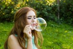 美丽的在summe的妇女吹的泡影在湖附近 免版税库存图片