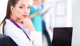 美丽的坐在书桌的年轻人微笑的女性医生 免版税库存图片