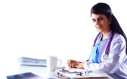 美丽的坐在书桌的年轻人微笑的女性医生 库存图片