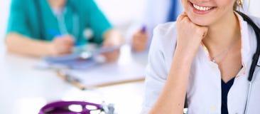 美丽的坐在书桌的年轻人微笑的女性医生 库存照片