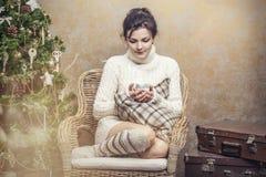 美丽的坐在的一把椅子的妇女饮用的茶或咖啡 免版税图库摄影