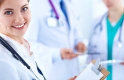 美丽的坐在的年轻人微笑的女性医生 免版税库存照片