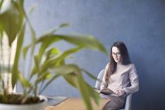 美丽的坐在顶楼办公室r的女实业家佩带的玻璃 免版税图库摄影