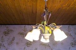 美丽的垂悬在一块木天花板的一盏被点燃的减速火箭的枝形吊灯的葡萄酒内部背景,有花的装饰的灯,家 免版税库存图片